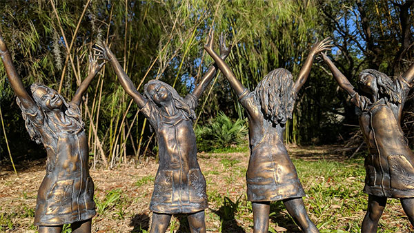 Bronze Statues Featuring Four Women with Their Hands in the Air